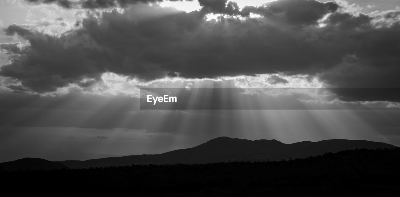 LOW ANGLE VIEW OF SUNLIGHT STREAMING THROUGH SILHOUETTE MOUNTAIN RANGE