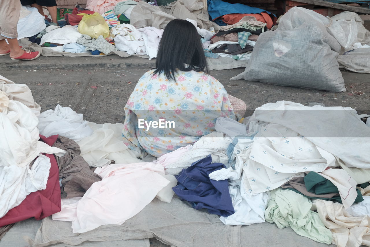Rear view of homeless woman with stacked clothes on footpath