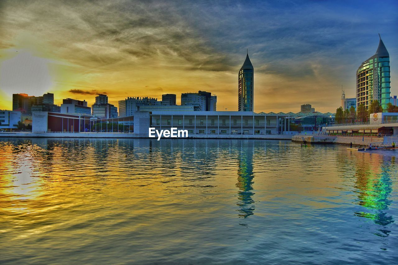 Scenic view of river by cityscape against sky during sunset