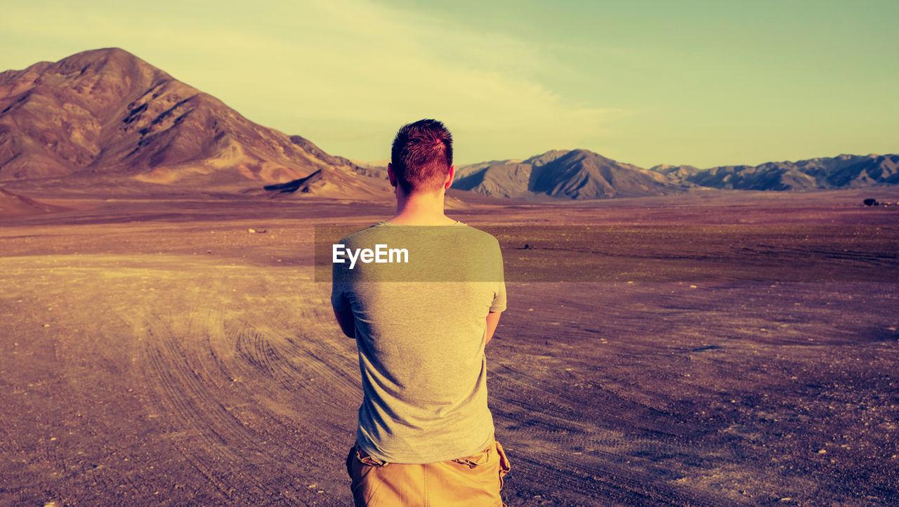 Rear View Of Man Standing On Barren Landscape Against Sky