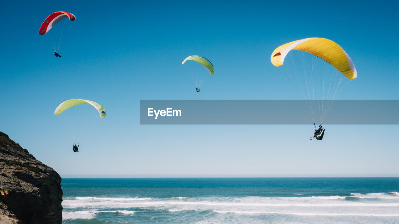 People Paragliding At Beach Against Clear Blue Sky