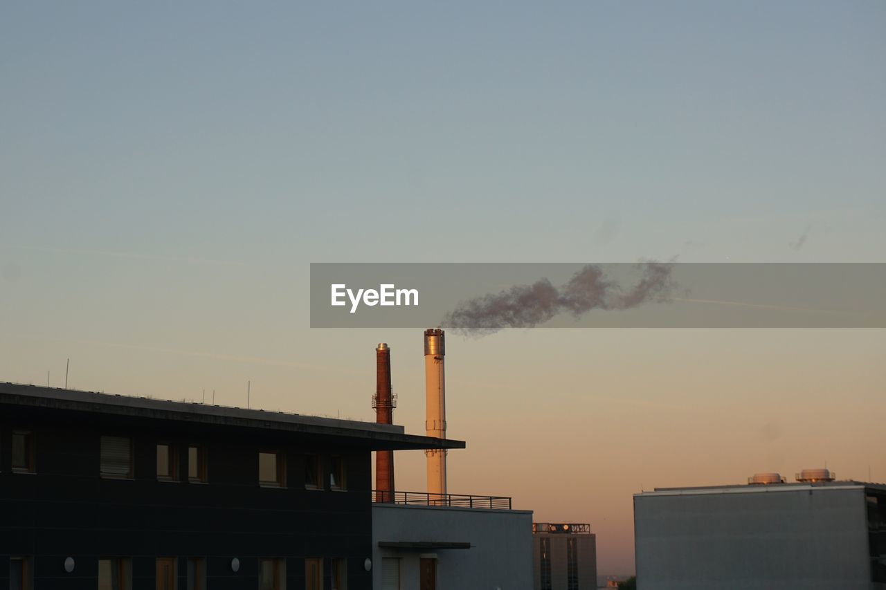 building exterior, built structure, architecture, factory, sky, smoke stack, industry, smoke - physical structure, chimney, pollution, emitting, environmental issues, no people, clear sky, nature, sunset, smoke, air pollution, environment, outdoors, fumes, atmospheric, ecosystem