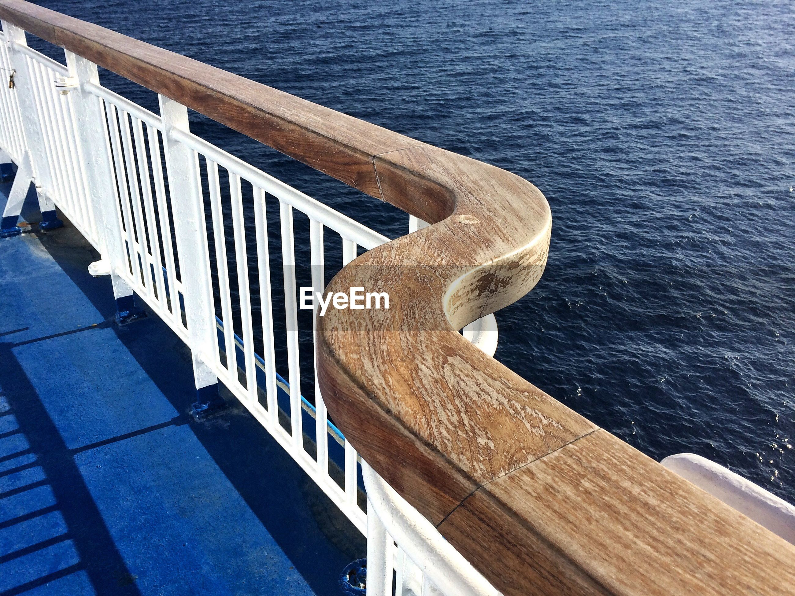 HIGH ANGLE VIEW OF WOODEN RAILING AGAINST SEA