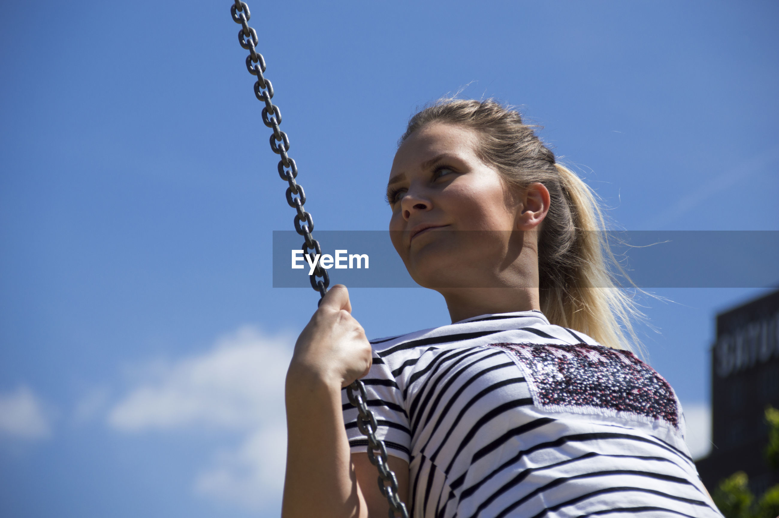 Low angle view of young woman looking away while swinging against sky
