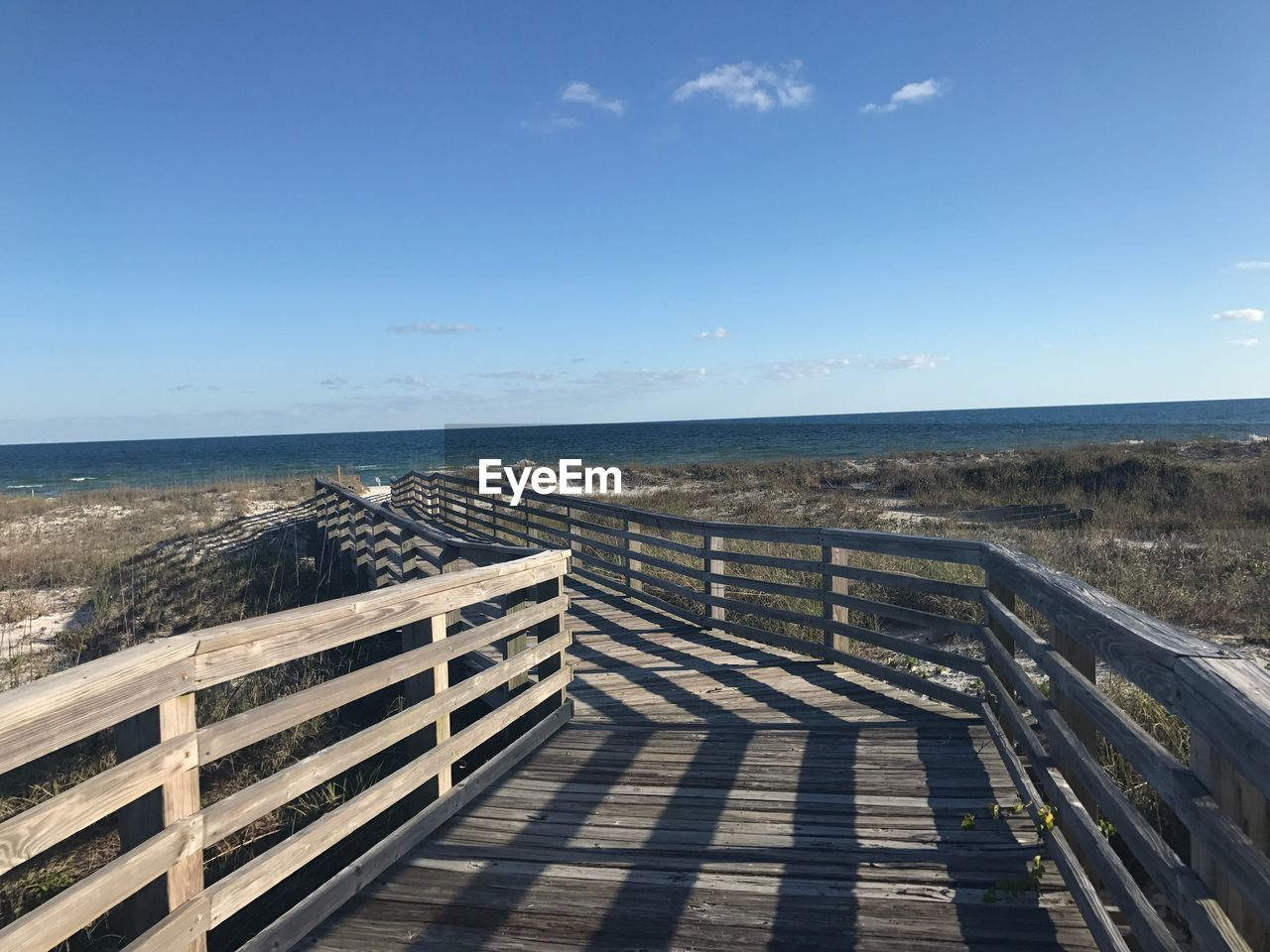 horizon over water, sea, railing, water, scenics, tranquility, day, tranquil scene, sky, nature, beauty in nature, outdoors, sunlight, beach, clear sky, no people, shadow