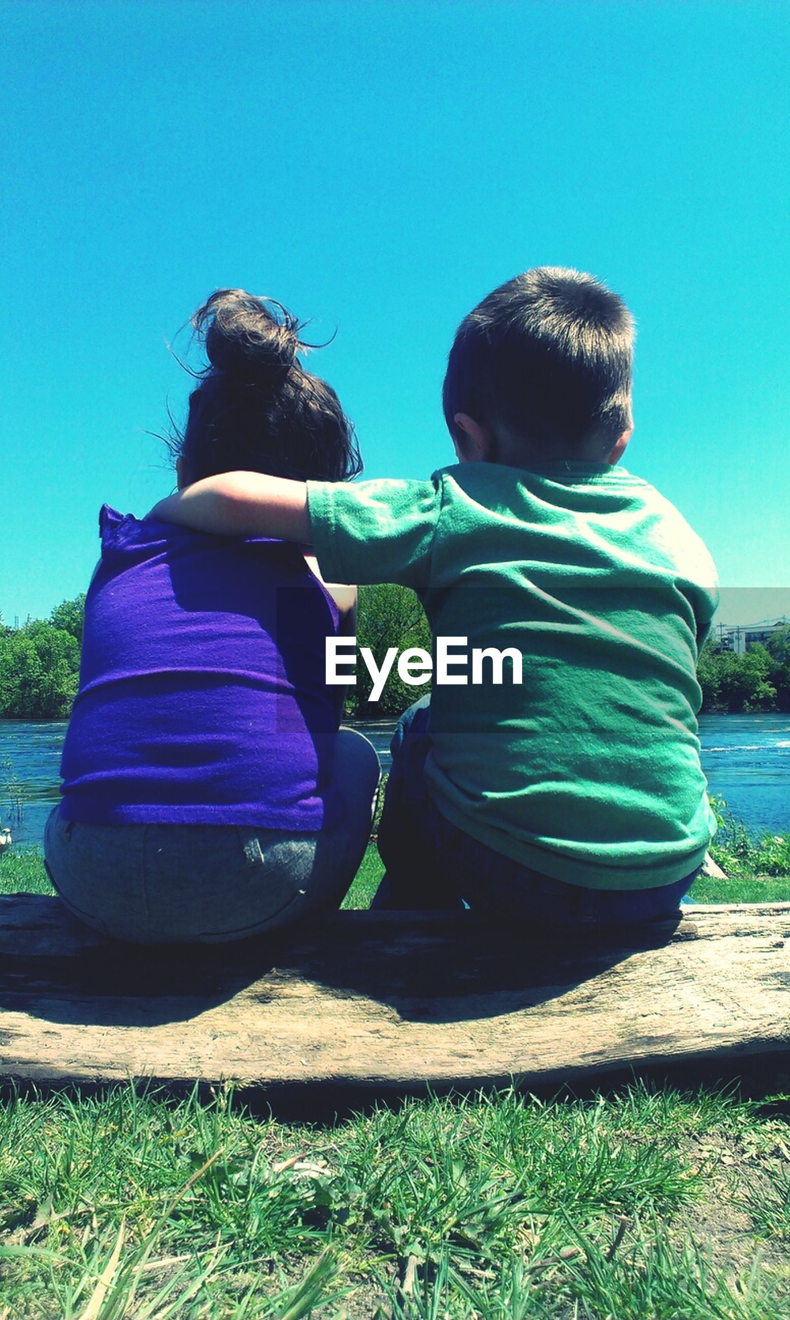 Rear view of two kids overlooking lake