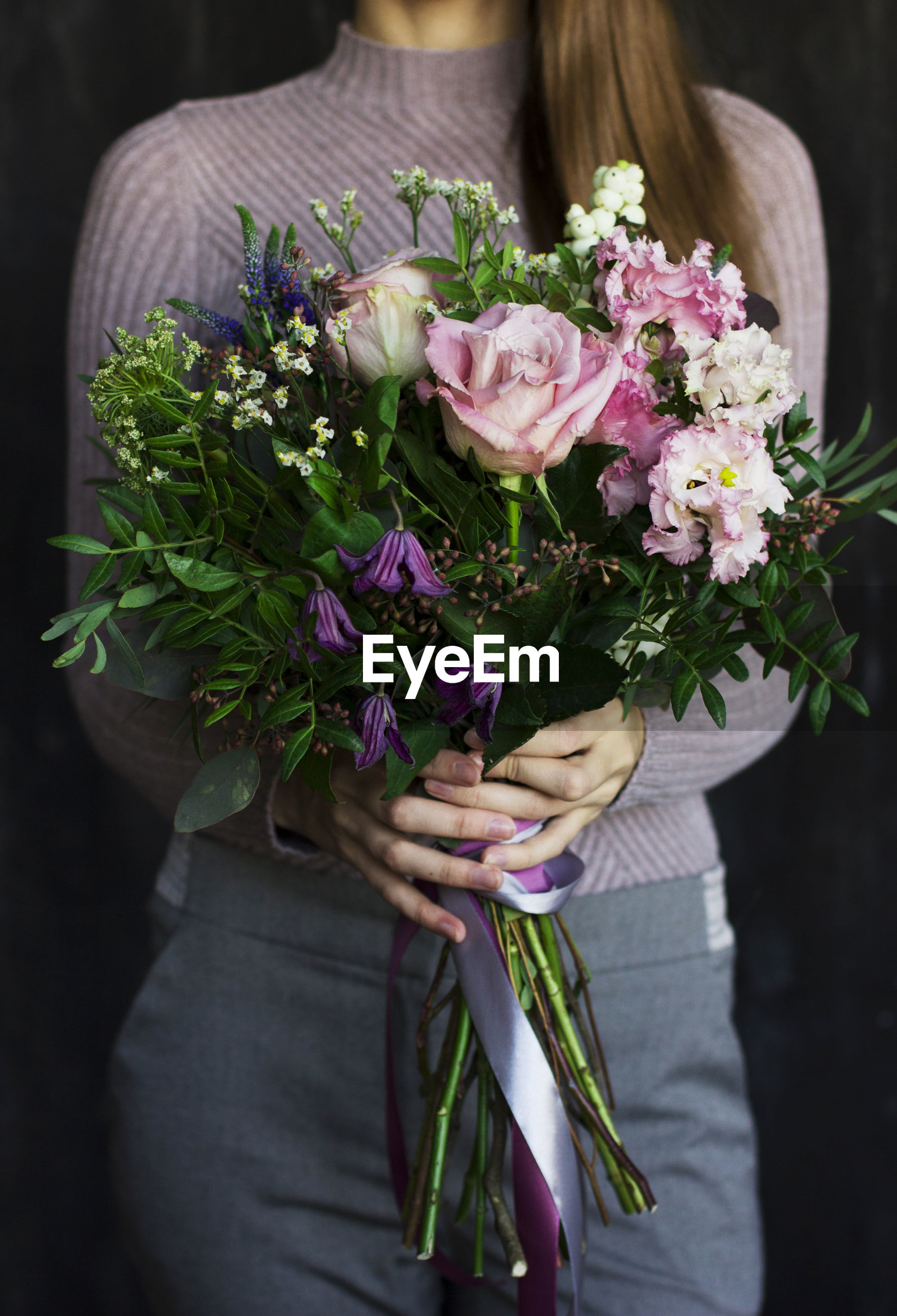 Midsection of woman holding bouquet against black background