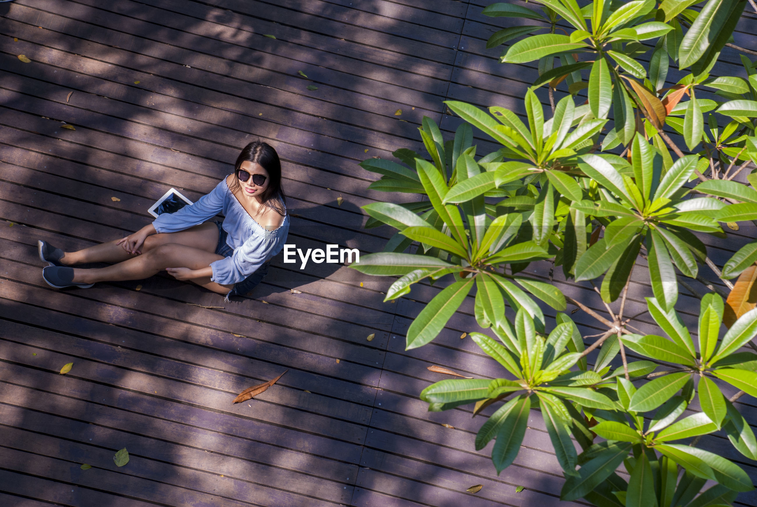 High angle view of woman wearing sunglasses with digital tablet sitting on boardwalk