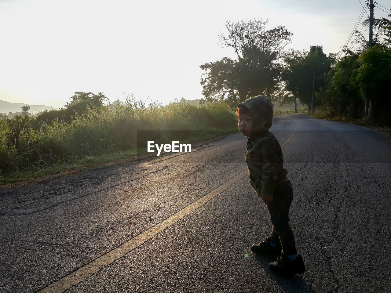 Side view of baby boy standing on road amidst trees
