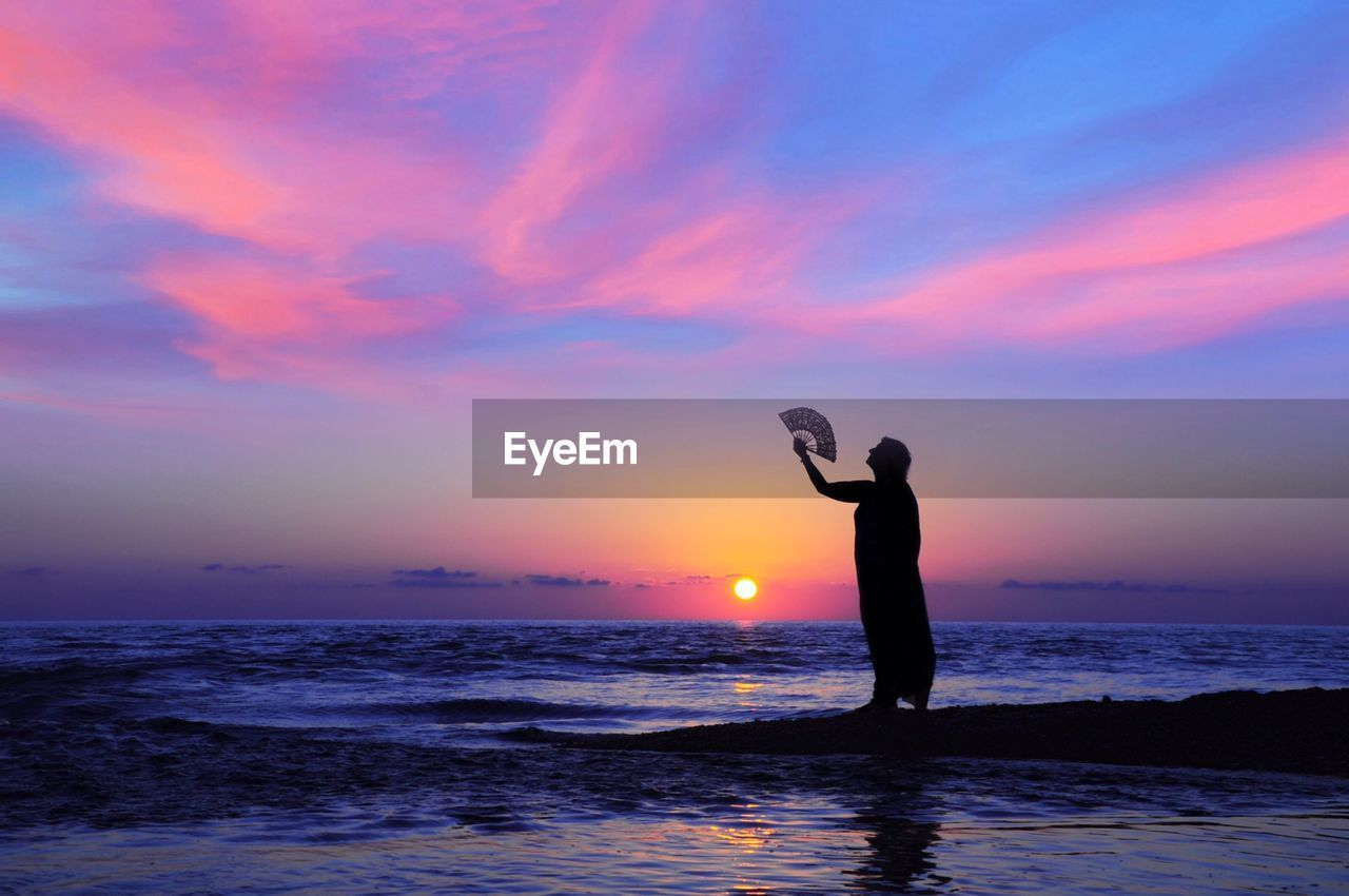 sunset, sky, sea, water, real people, beauty in nature, scenics - nature, silhouette, standing, horizon over water, orange color, lifestyles, horizon, one person, land, beach, leisure activity, cloud - sky, nature, arms raised, human arm, outdoors