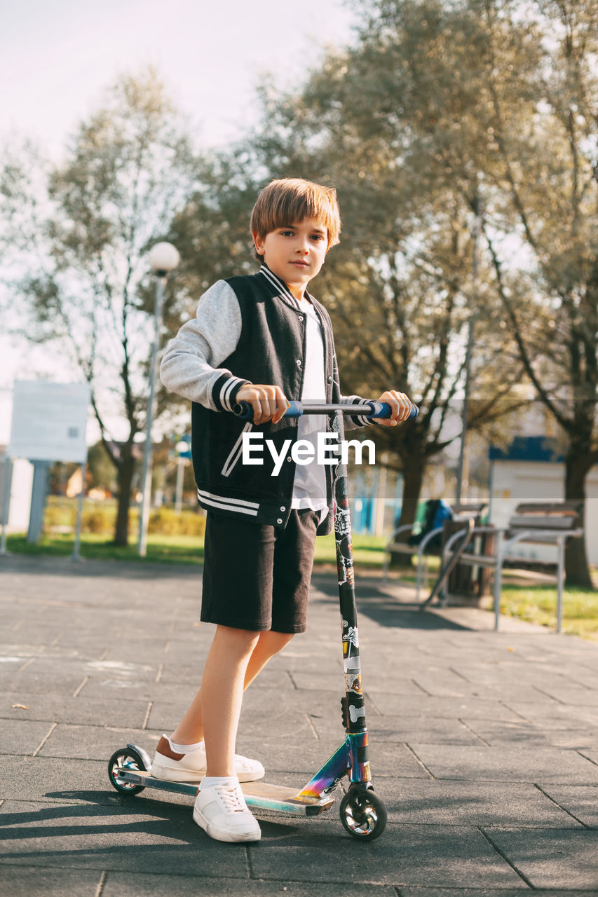 FULL LENGTH OF BOY STANDING WITH UMBRELLA ON STREET