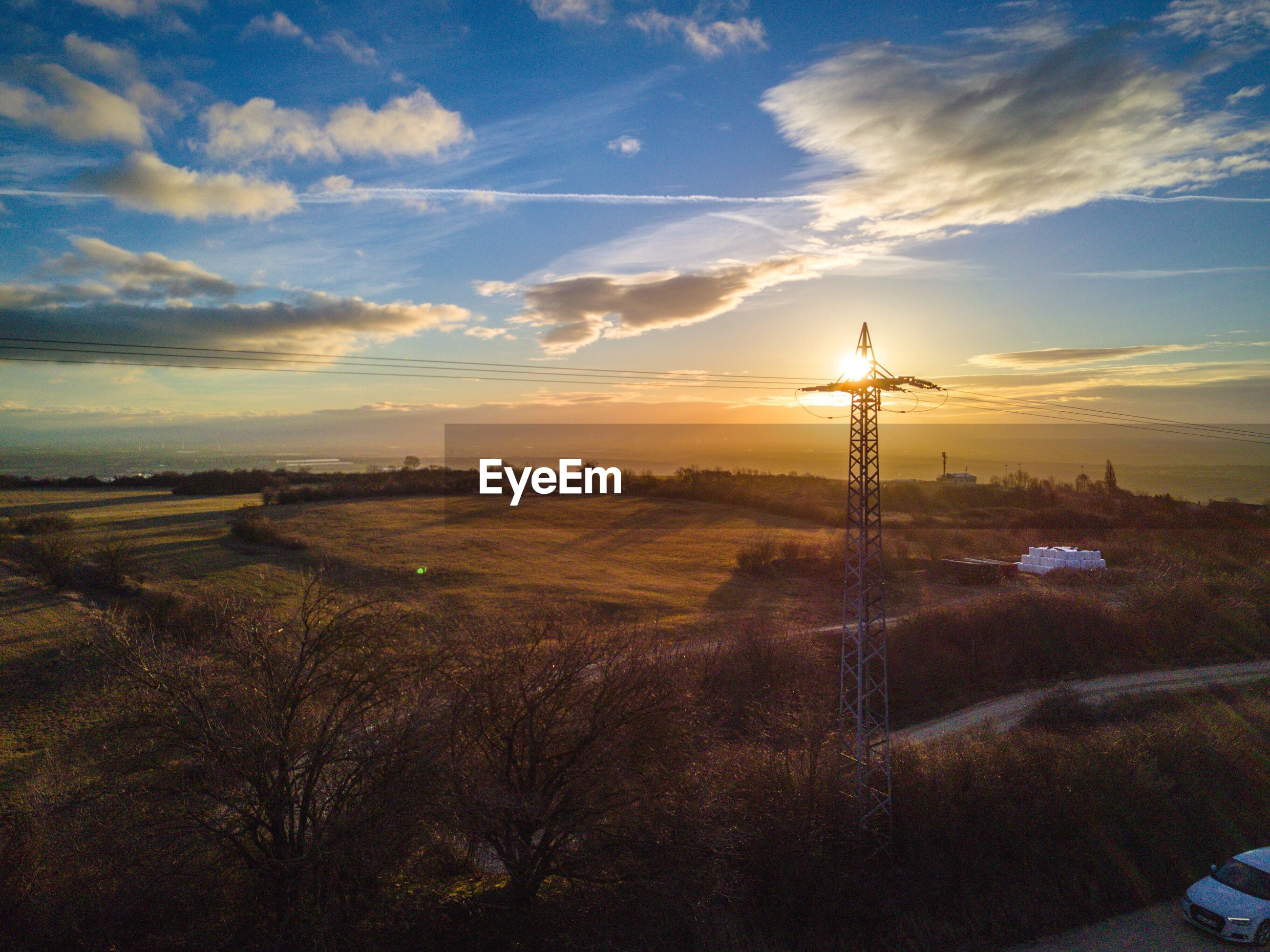 ELECTRICITY PYLONS ON LANDSCAPE AGAINST SKY
