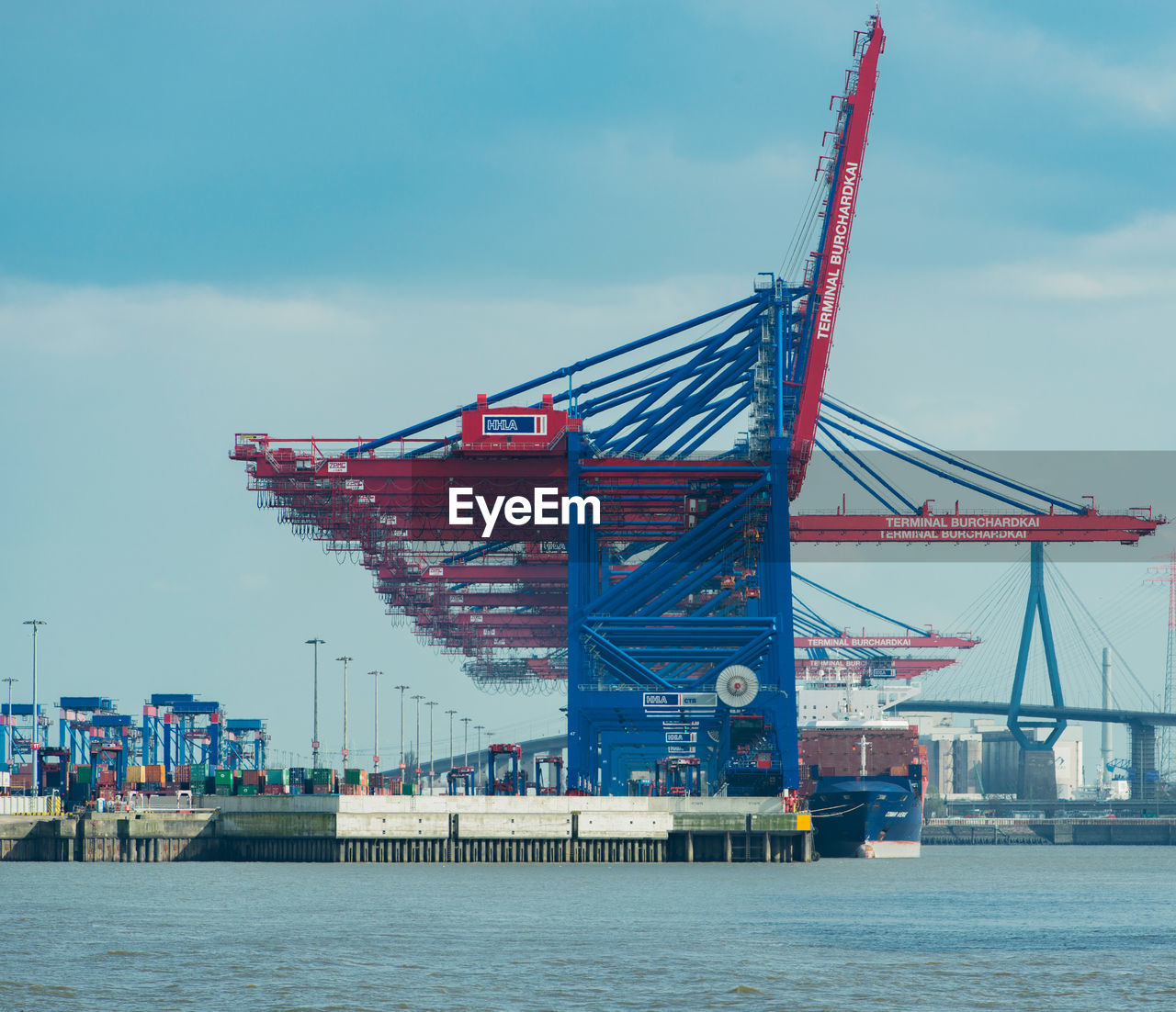 transportation, sky, built structure, cloud - sky, commercial dock, water, waterfront, architecture, nautical vessel, day, mode of transport, crane - construction machinery, river, freight transportation, outdoors, shipping, harbor, cargo container, no people, building exterior, city, industry, cityscape, shipyard