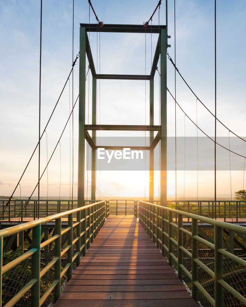 Footbridge against sky at sunset