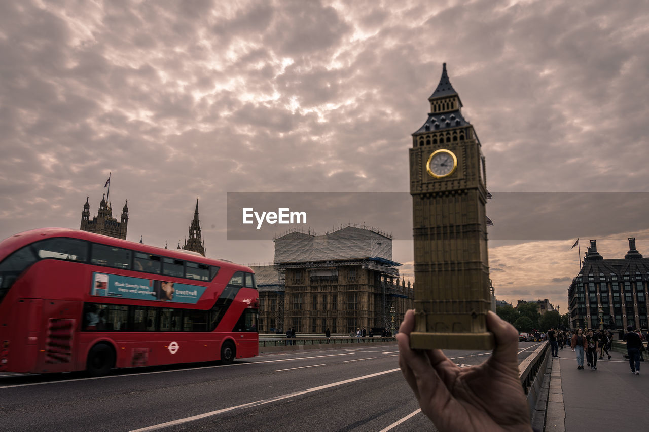 architecture, city, building exterior, built structure, clock tower, tower, sky, transportation, travel, mode of transportation, cloud - sky, tourism, travel destinations, building, real people, land vehicle, city life, unrecognizable person, tall - high, double-decker bus, hand, outdoors, clock