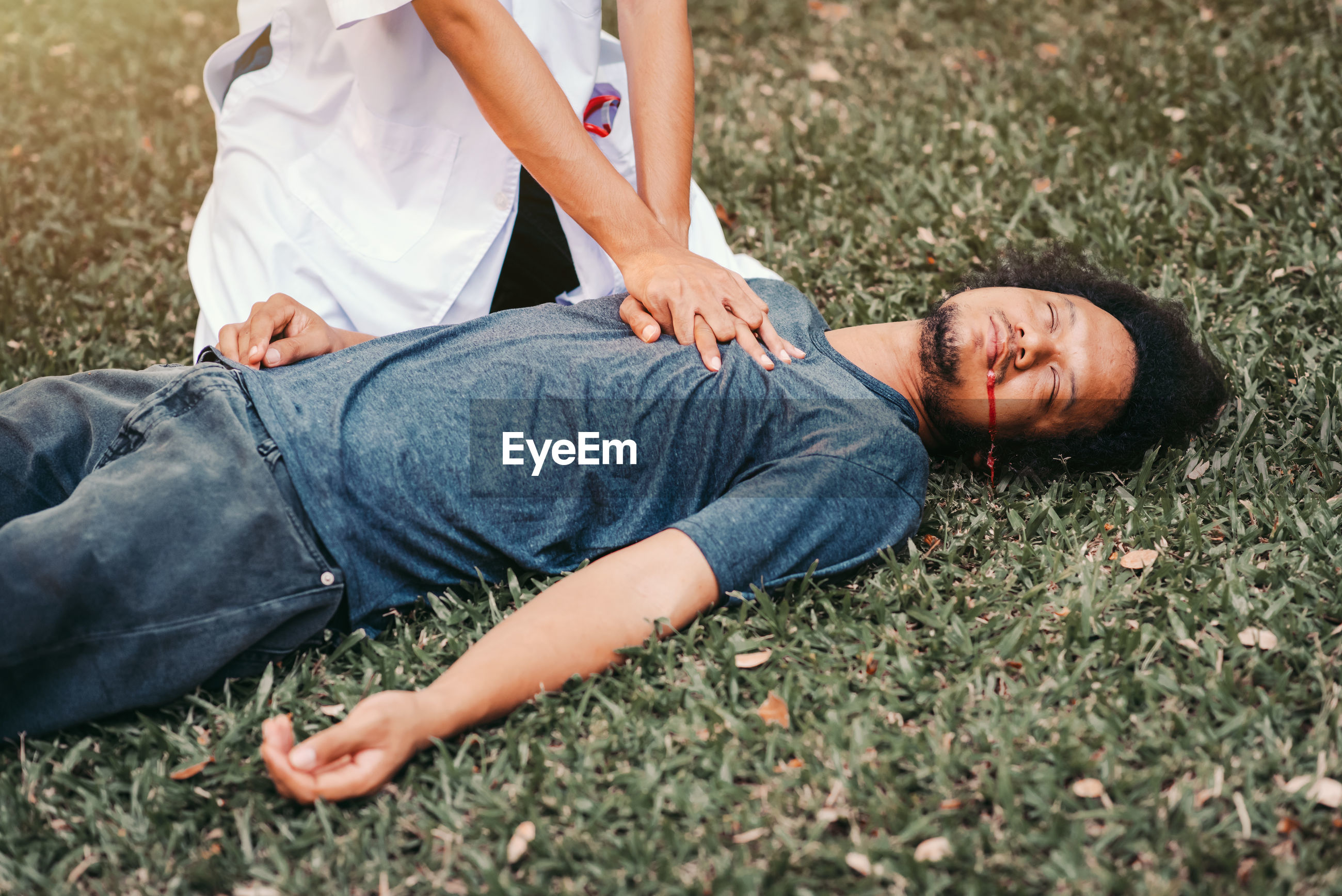 Midsection of doctor performing car on patient lying down at grass outdoors