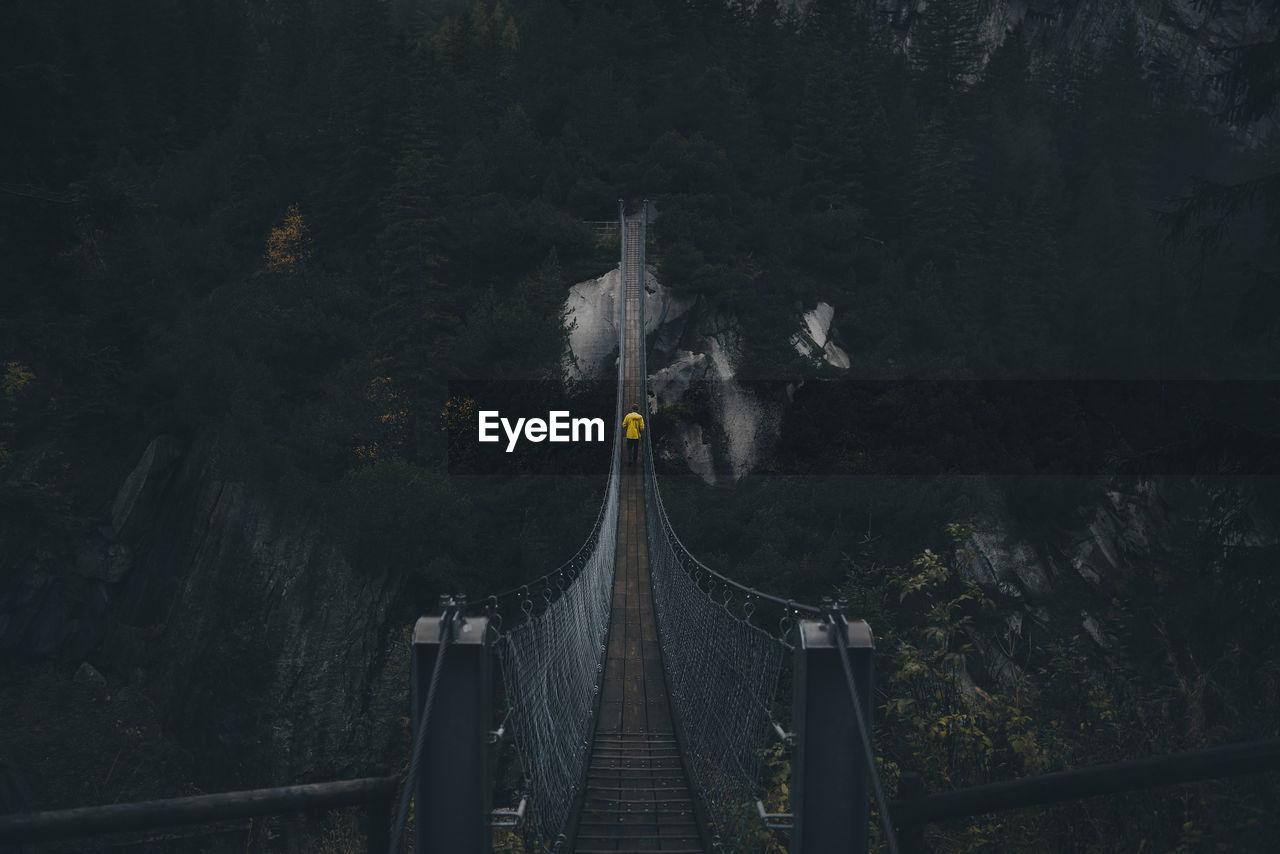 Rear View Of Man Walking On Rope Bridge