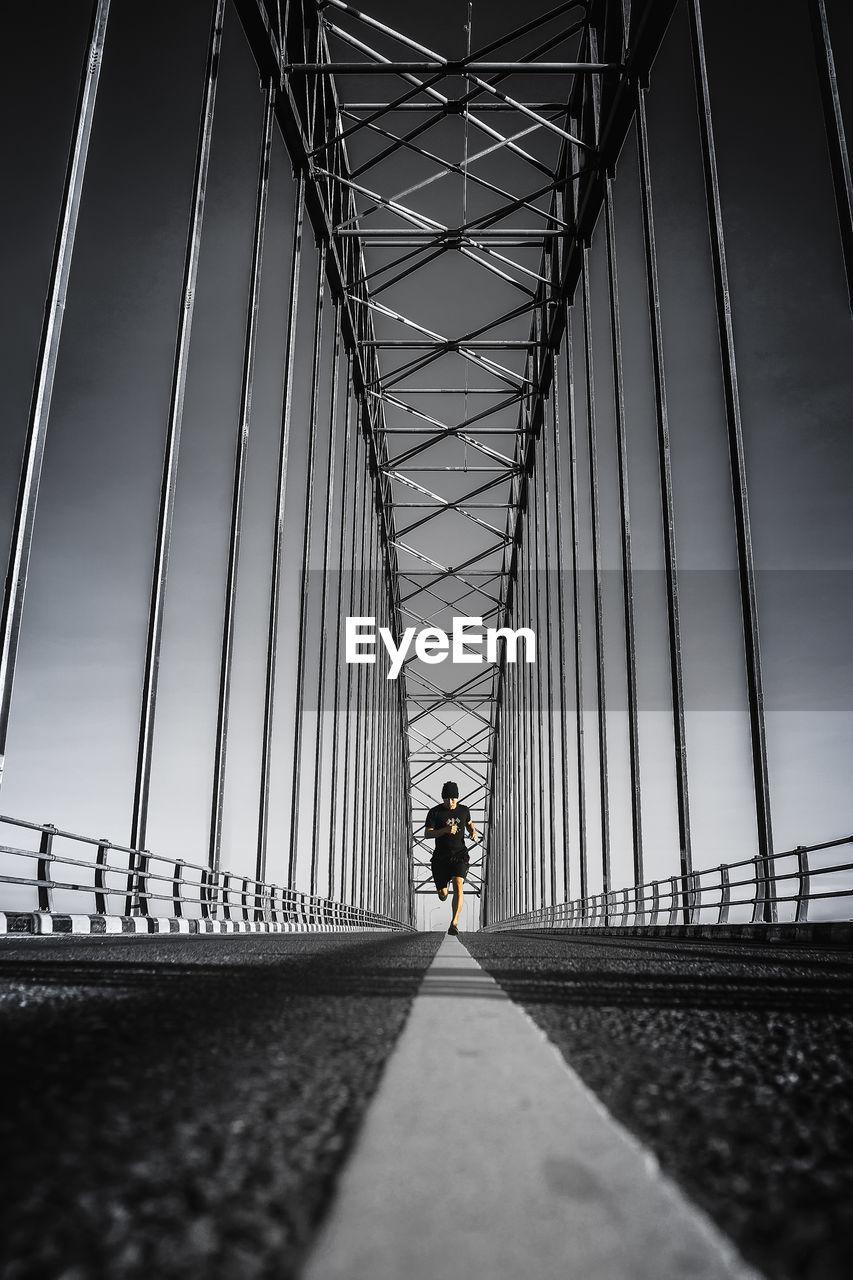 Man running on bridge against sky