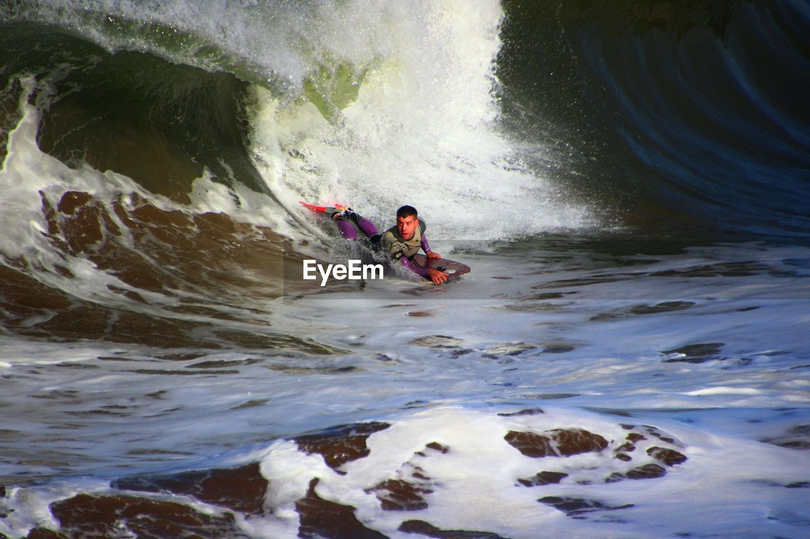 water, lifestyles, leisure activity, motion, adventure, men, extreme sports, vacations, full length, rock - object, waterfront, wave, recreational pursuit, high angle view, nature, splashing, surf, speed