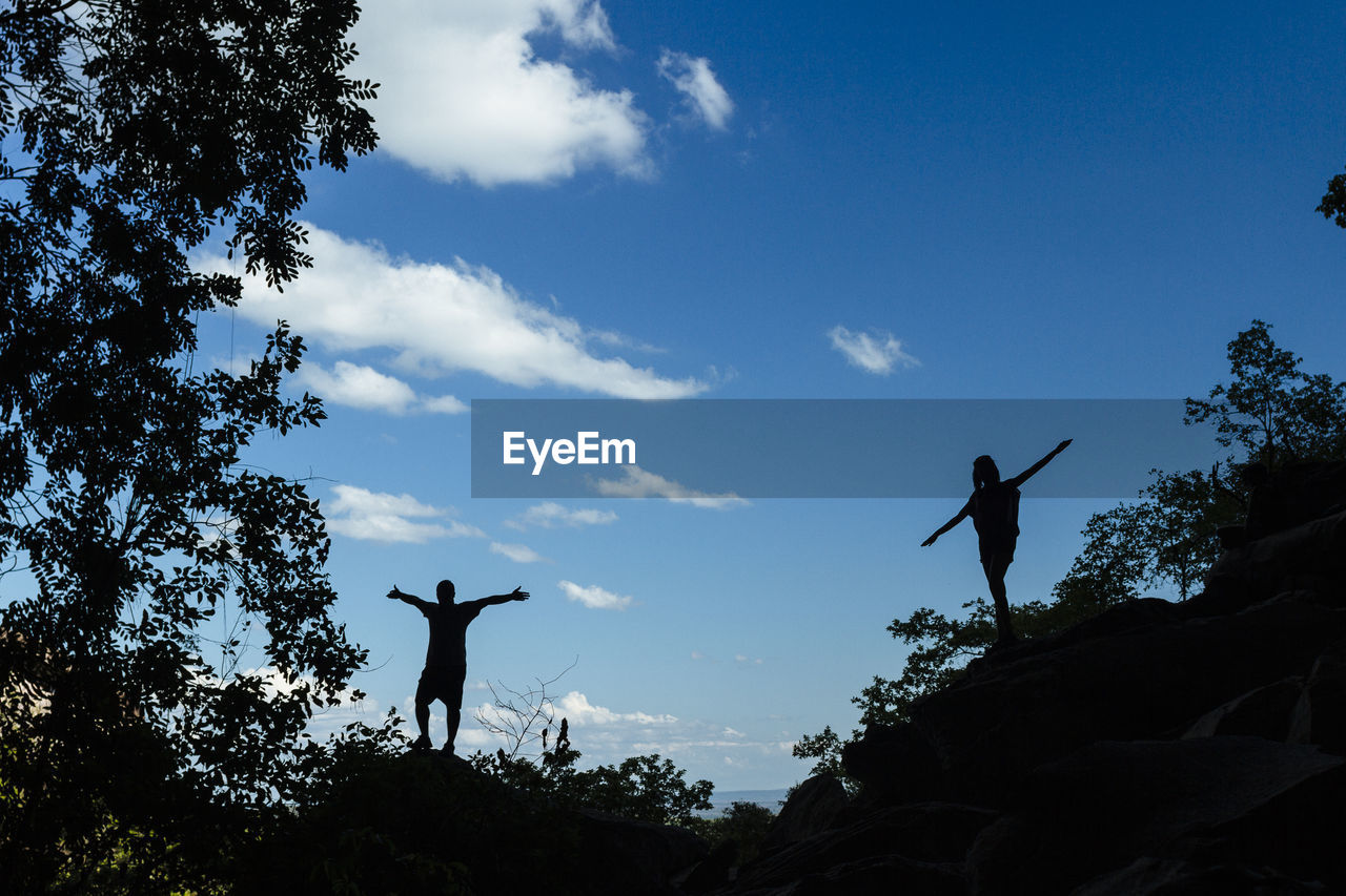 silhouette, leisure activity, arms outstretched, outdoors, real people, sky, full length, tree, jumping, men, low angle view, day, standing, lifestyles, nature, energetic, people
