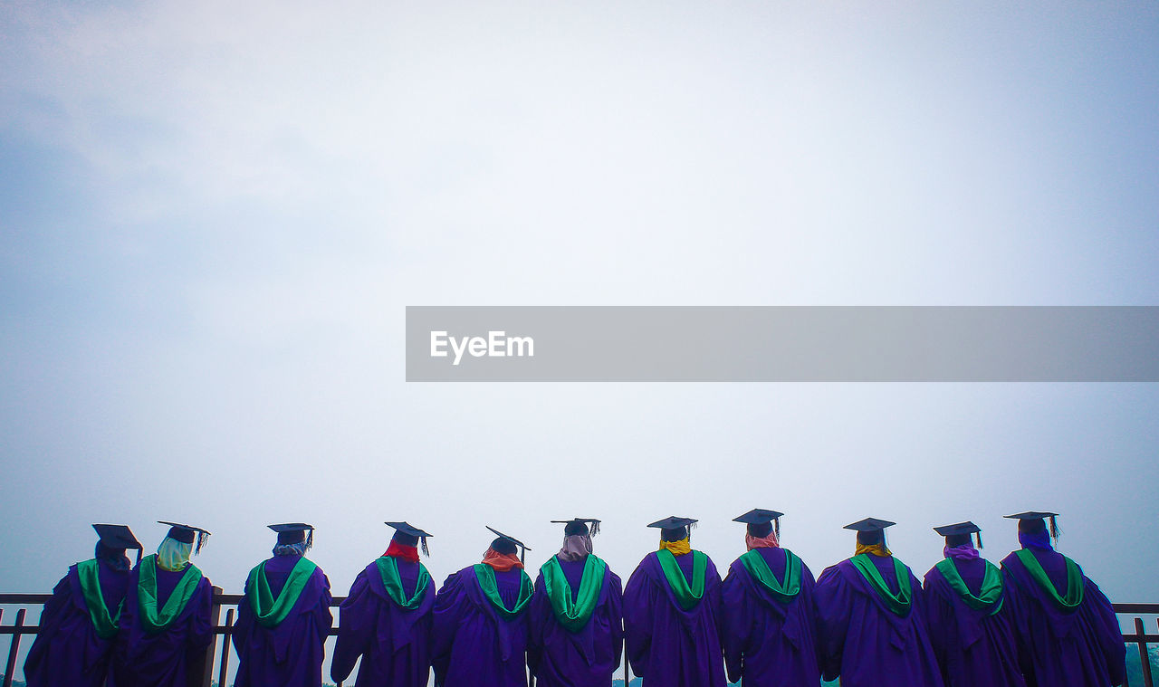 Rear View Of People Wearing Graduation Gowns