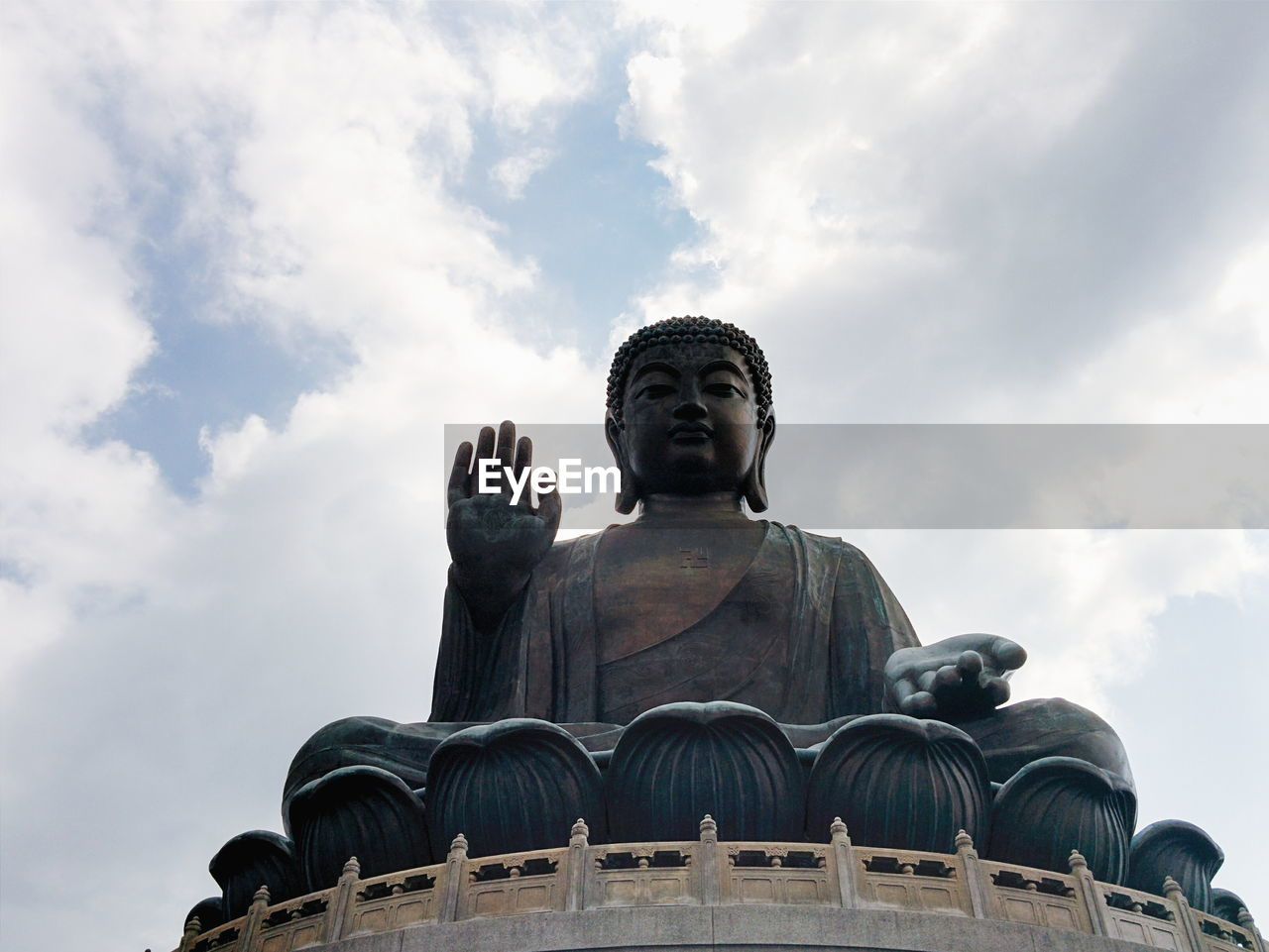 Low Angle View Of Tian Tan Buddha Against Cloudy Sky