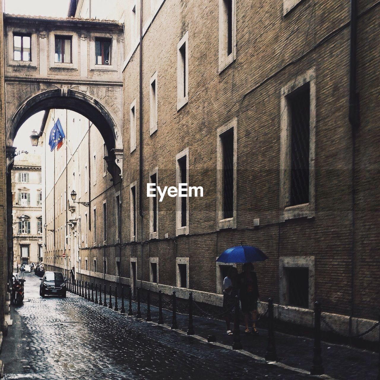 Couple Holding Umbrella While Walking On Sidewalk