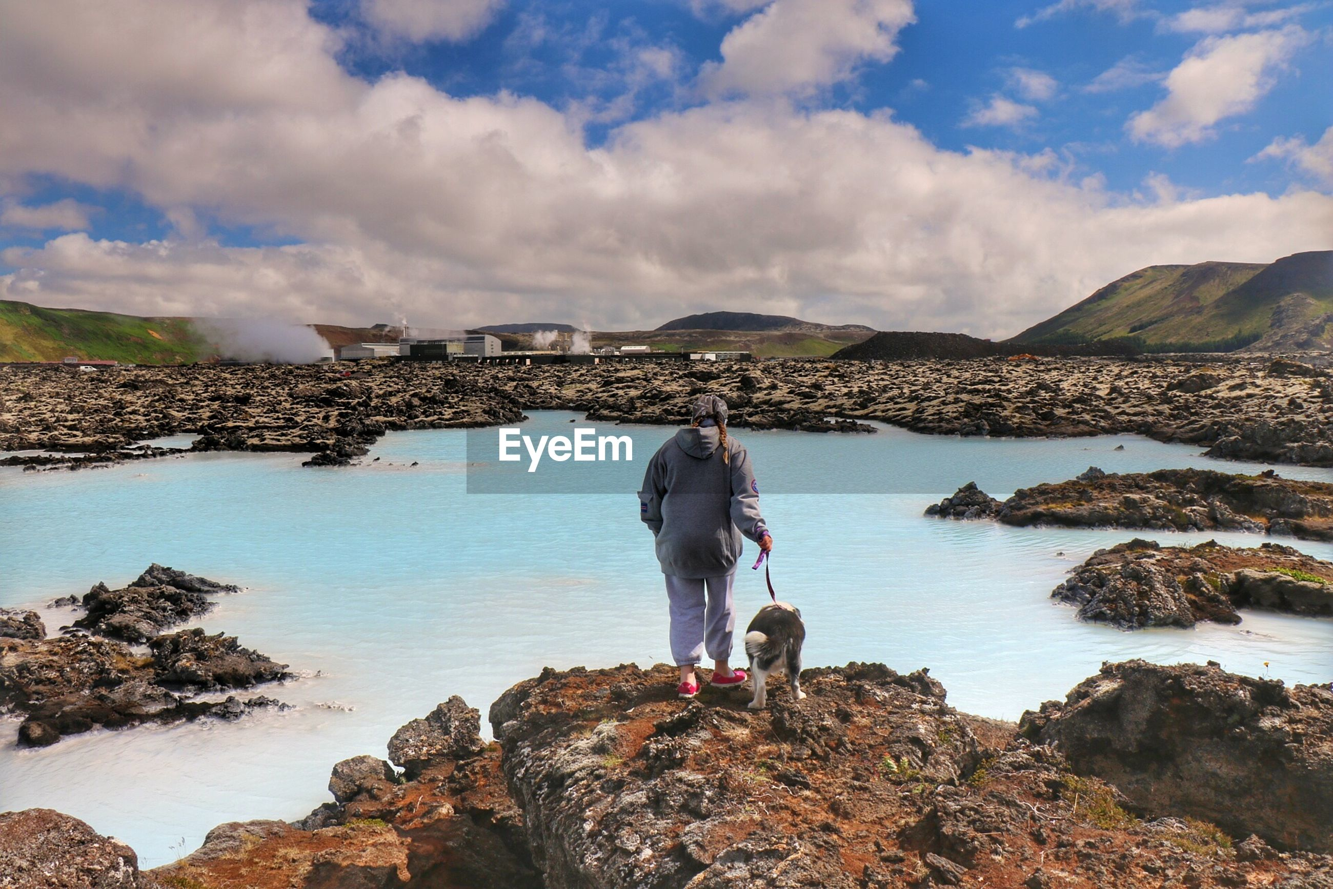 Rear view of girl with dog standing on rocks by lake at blue lagoon
