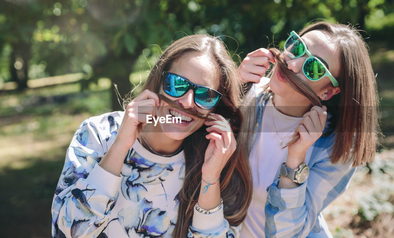 Portrait Of Friends Wearing Sunglasses While Holding Their Hair As Mustache At Park