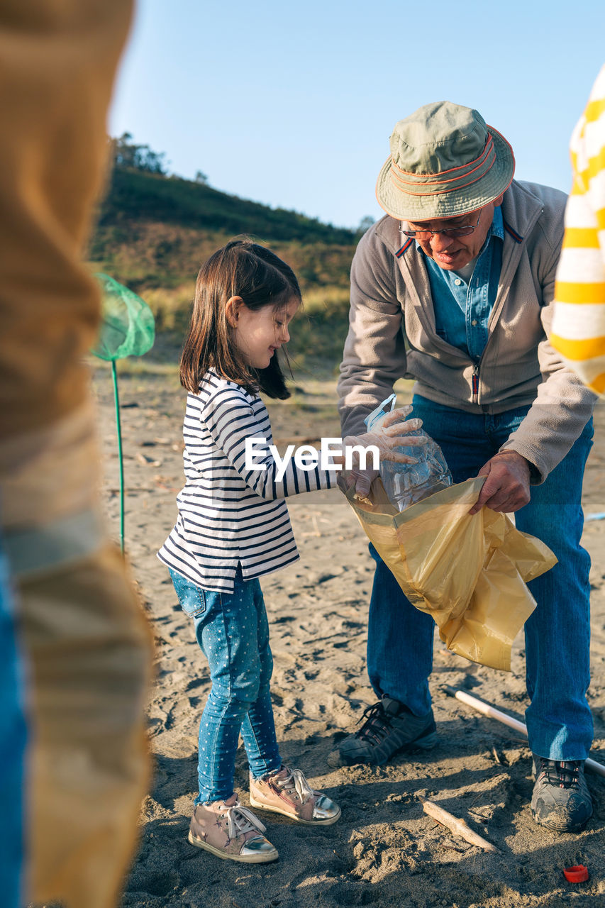 Granddaughter assisting grandfather while cleaning beach