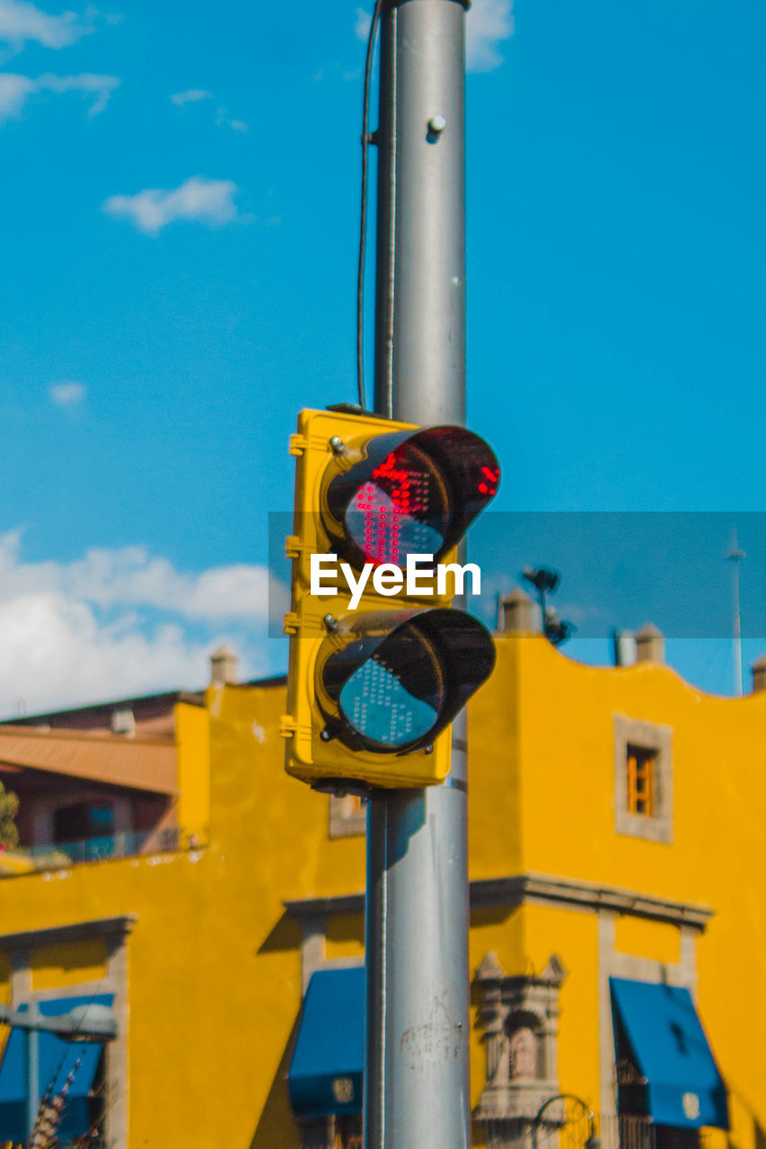Close-up of road signal against blue sky