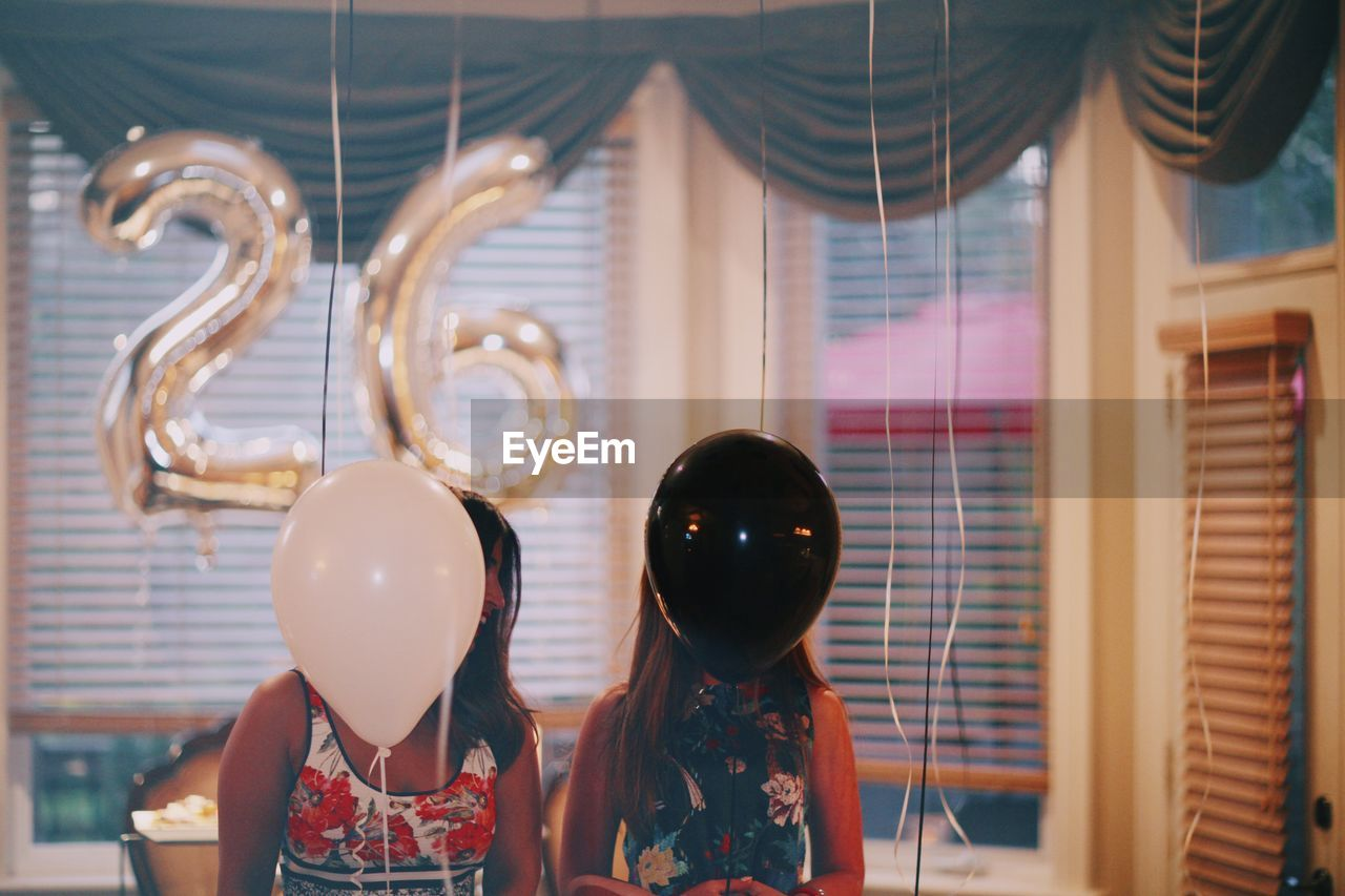 Friends Covering Their Face With Balloons