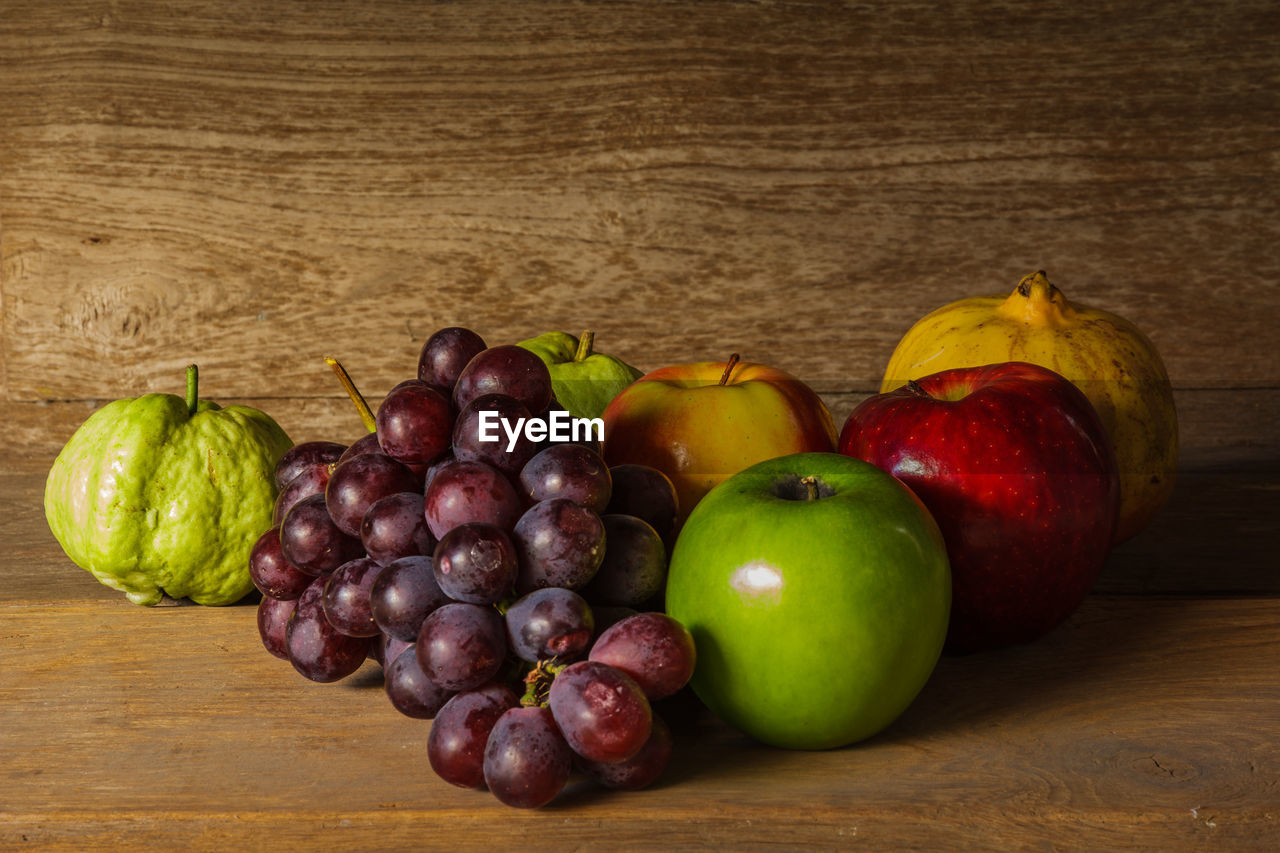 food, healthy eating, food and drink, fruit, wellbeing, freshness, table, still life, wood - material, indoors, no people, apple - fruit, close-up, grape, red, choice, variation, large group of objects, group of objects, green color, apple, ripe