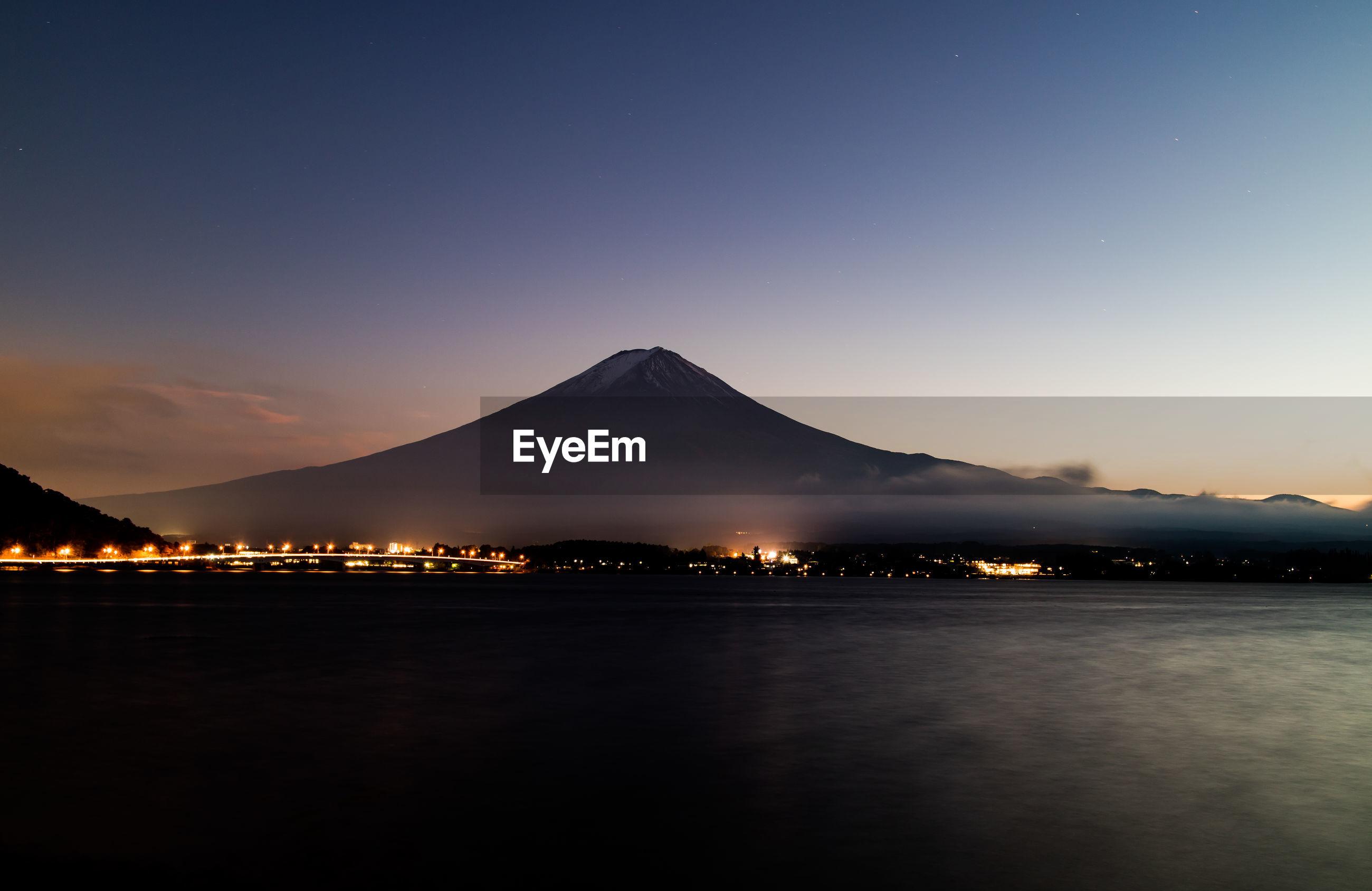 ILLUMINATED MOUNTAIN AGAINST SKY AT NIGHT
