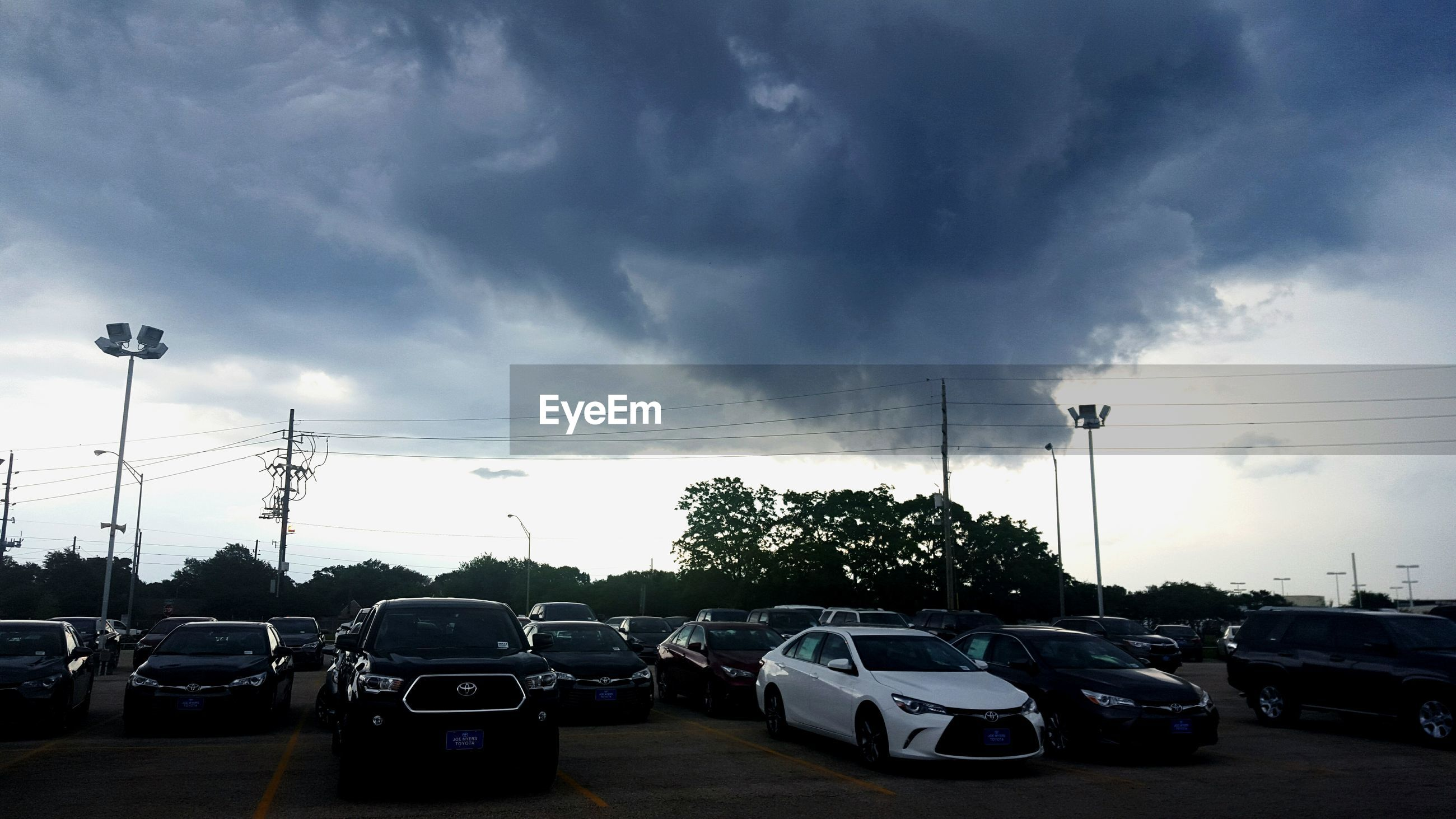 transportation, car, land vehicle, mode of transport, sky, cloud - sky, street, street light, road, cloudy, parking, parking lot, stationary, parked, cloud, traffic, travel, outdoors, in a row, weather