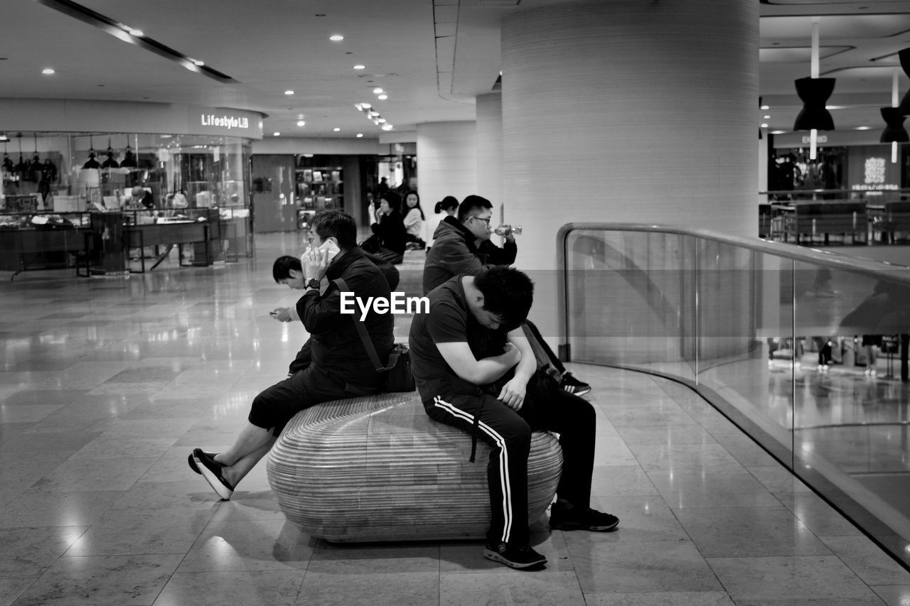 PEOPLE SITTING ON SHOPPING MALL