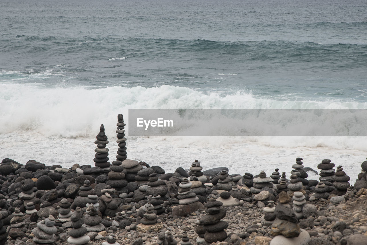 sea, water, rock, solid, beach, land, beauty in nature, rock - object, wave, motion, stone - object, nature, scenics - nature, pebble, stone, aquatic sport, tranquility, surfing, day, power in nature, groyne, flowing water