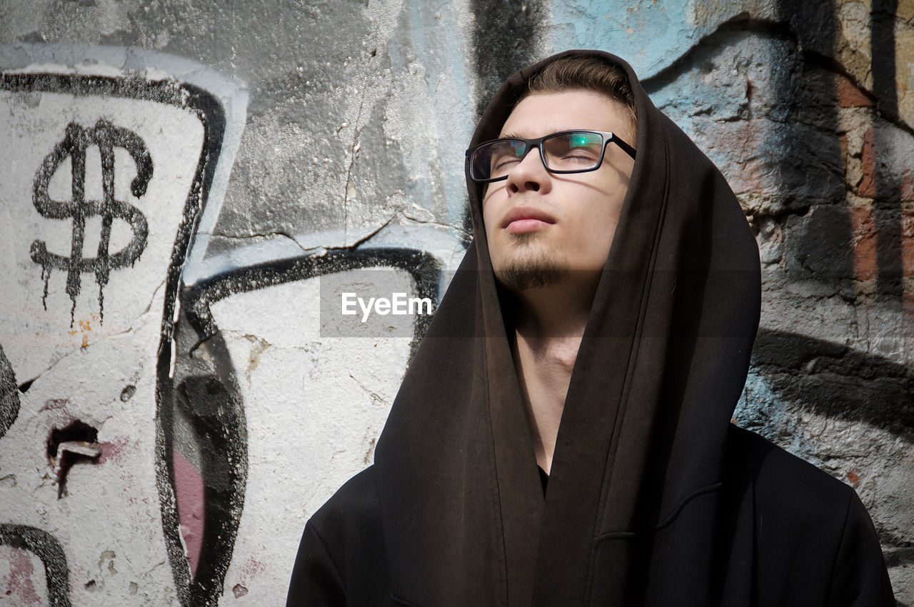 wall - building feature, one person, graffiti, young adult, glasses, eyeglasses, real people, portrait, front view, lifestyles, young men, leisure activity, looking, headshot, standing, adult, beard, creativity, contemplation, hairstyle, teenager, hood - clothing