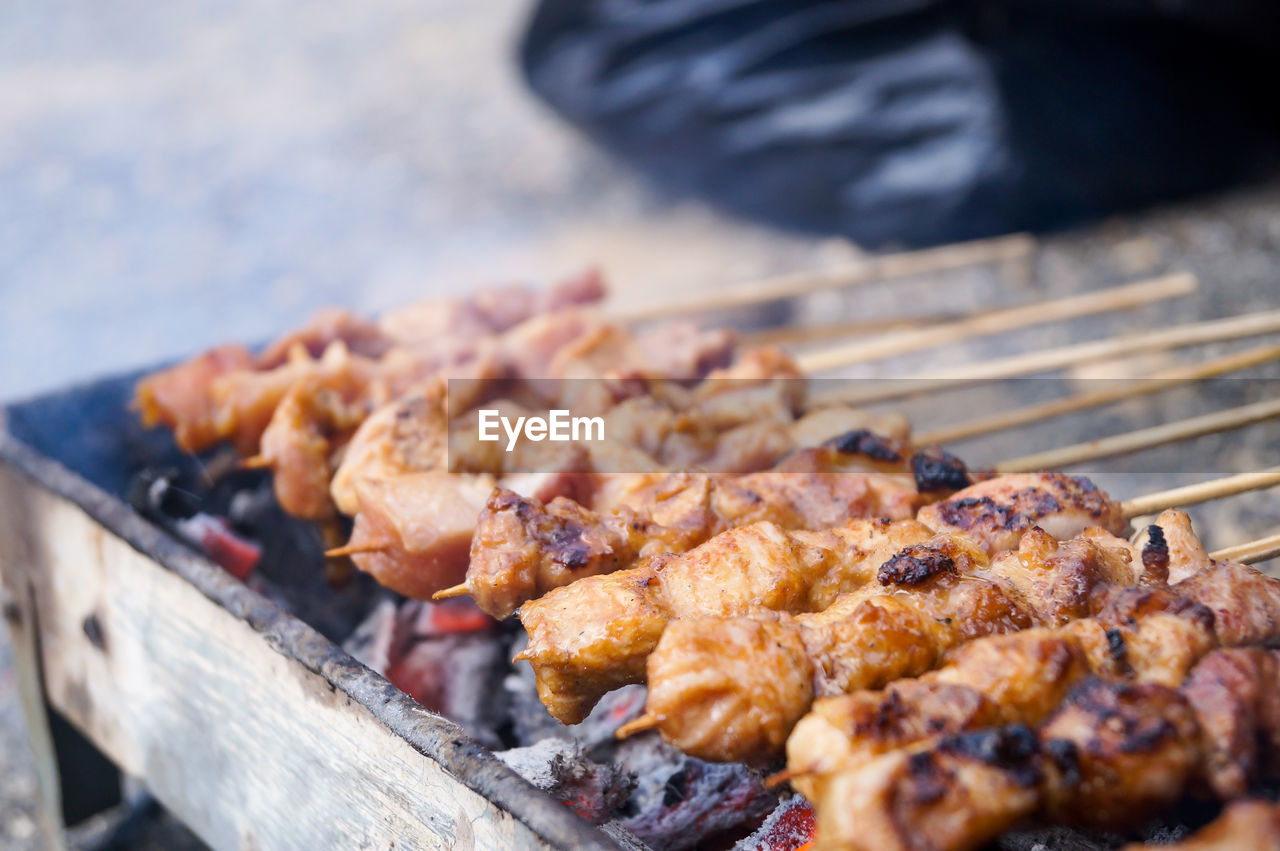 CLOSE-UP OF MEAT COOKING ON BARBECUE