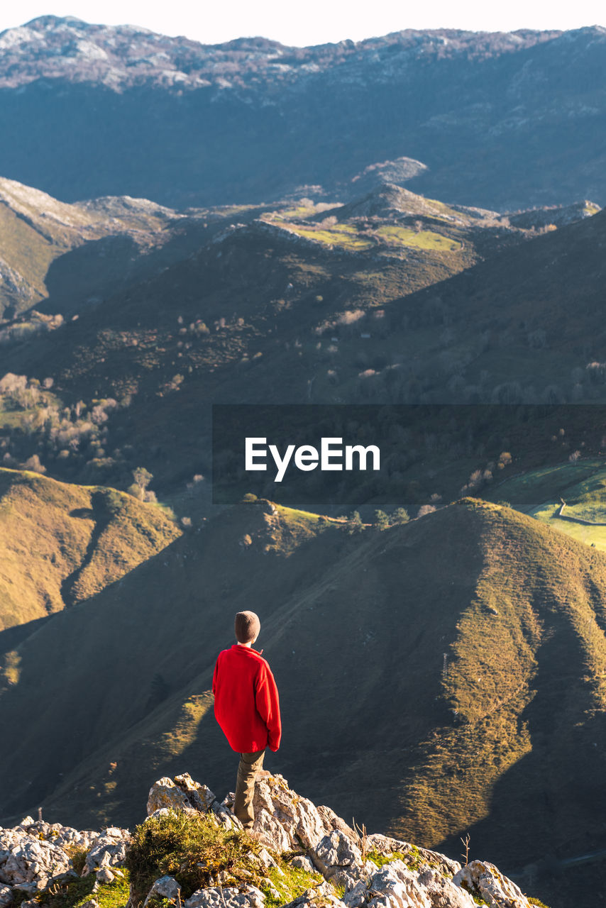 REAR VIEW OF PERSON LOOKING AT MOUNTAINS