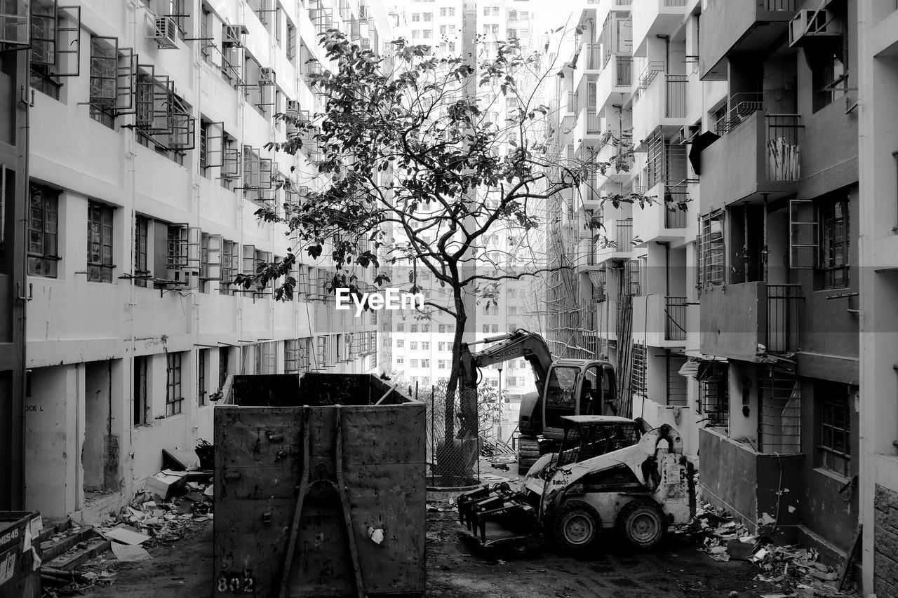 building exterior, architecture, built structure, building, mode of transportation, transportation, land vehicle, city, day, motor vehicle, residential district, outdoors, car, nature, plant, tree, window, no people, abandoned, street, apartment
