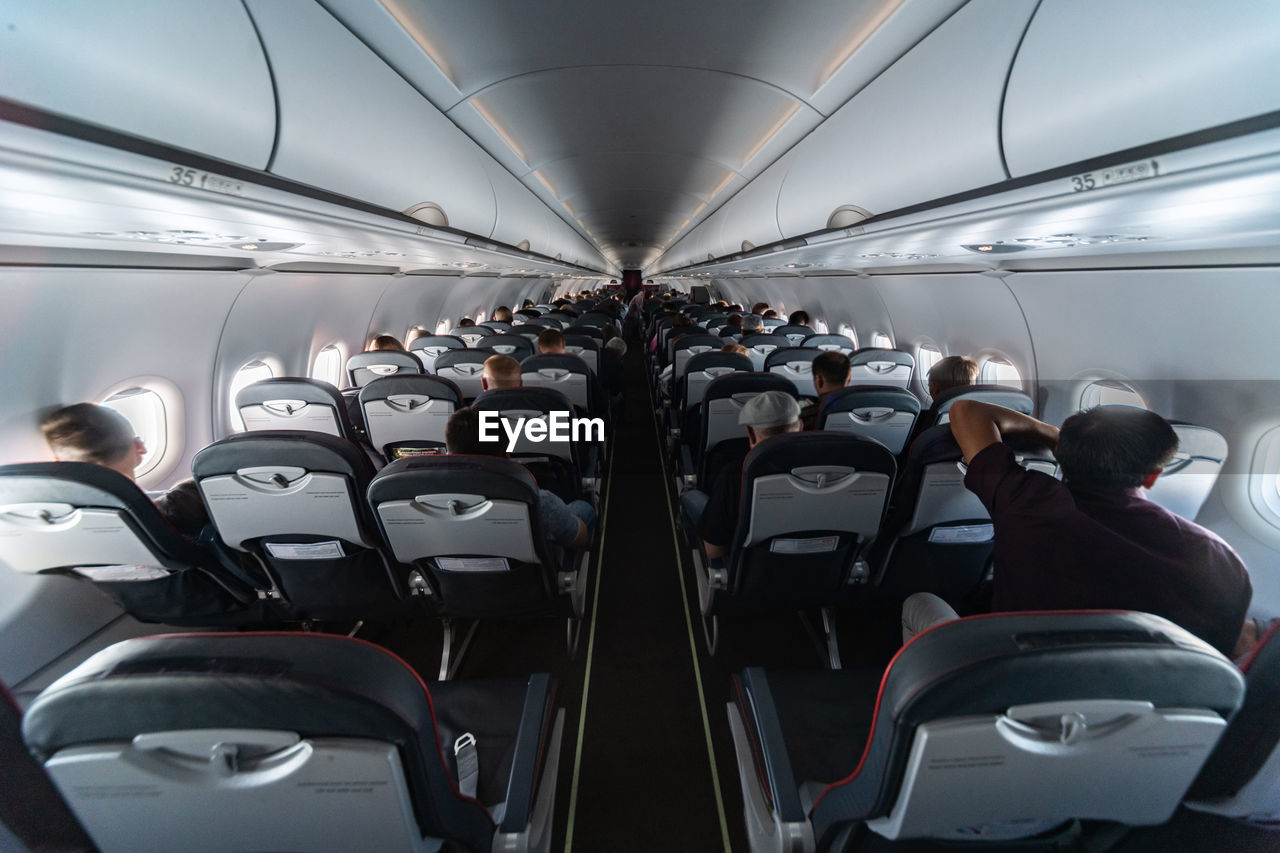 mode of transportation, transportation, vehicle interior, travel, seat, vehicle seat, public transportation, land vehicle, real people, rear view, men, sitting, people, lifestyles, journey, airplane, outdoors, air vehicle, group of people, window