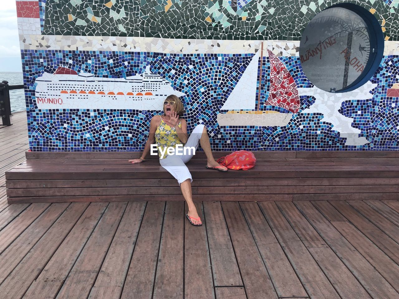 Full length of senior woman screaming while sitting against tiled wall on promenade