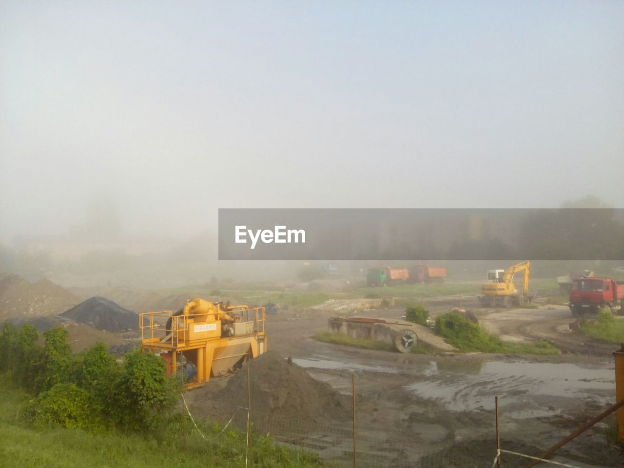 High angle view of earth movers on field during foggy weather