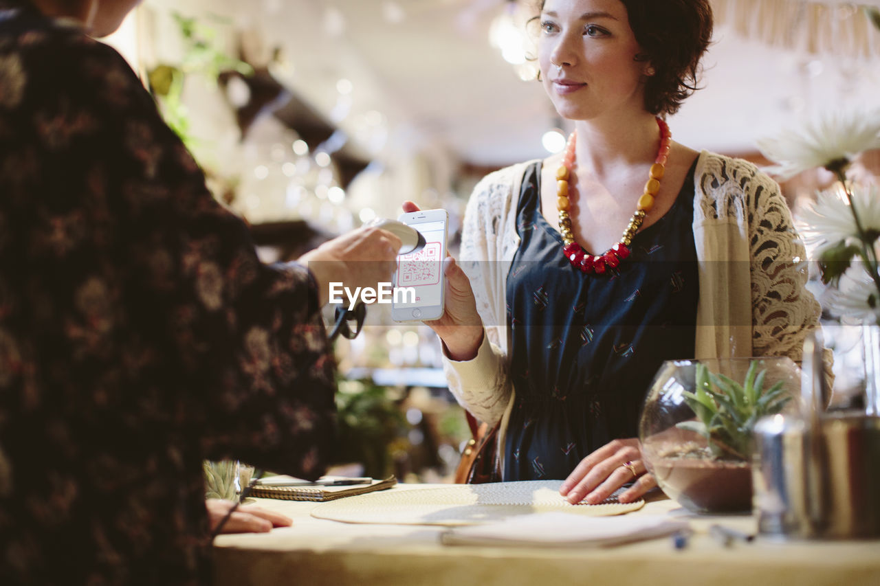 women, real people, business, indoors, selective focus, adult, table, people, front view, holding, waist up, food and drink, occupation, females, standing, lifestyles, restaurant, young adult, food