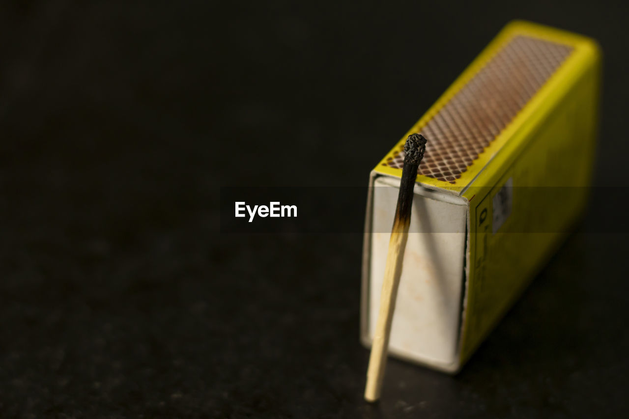 CLOSE-UP OF YELLOW BOX ON TABLE AGAINST BLACK BACKGROUND
