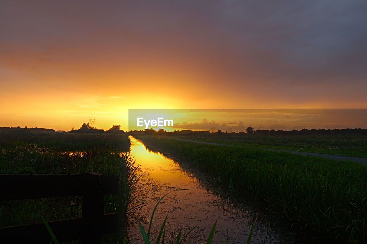 SCENIC VIEW OF AGRICULTURAL FIELD AGAINST ORANGE SKY