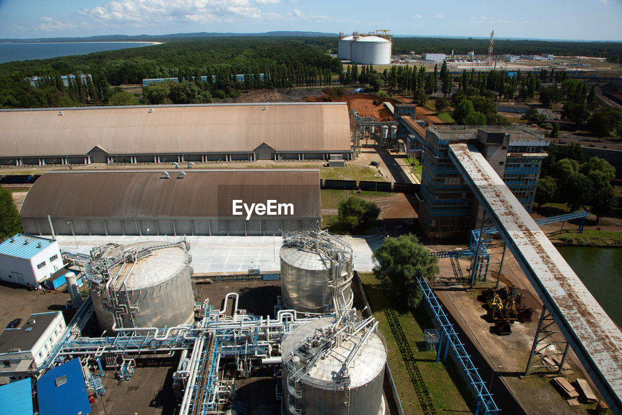 industry, high angle view, factory, built structure, architecture, day, fuel and power generation, nature, no people, sunlight, building exterior, outdoors, storage tank, water, metal, transportation, machinery, industrial building, sky, container, industrial equipment, pollution