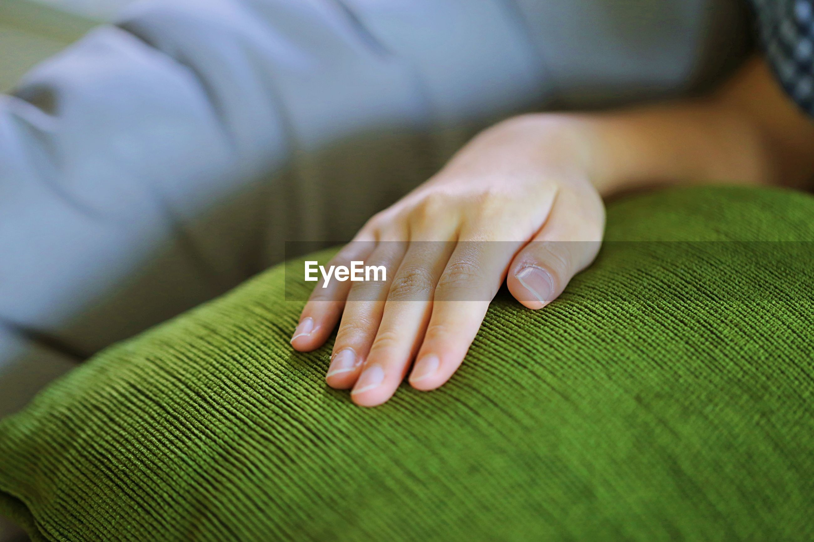 Cropped hand of woman on cushion