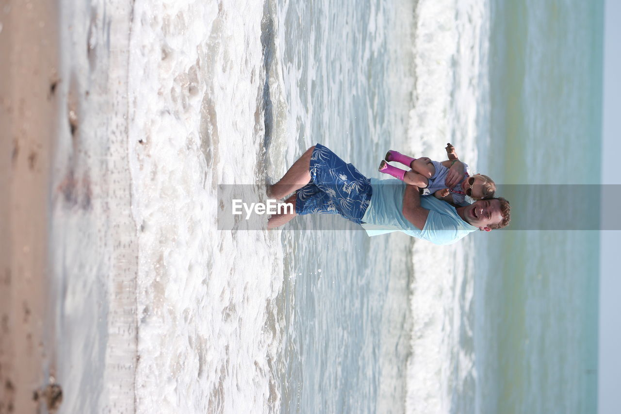 sea, water, beach, leisure activity, day, vacations, one person, nature, fun, outdoors, enjoyment, real people, wave, weekend activities, motion, cheerful, happiness, lifestyles, smiling, horizon over water, beauty in nature, childhood, full length, young women, young adult, sky, people